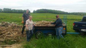 """Louise Boisvert, avec l'aide de trois bénévoles (le photographe), remplissent un """"trailer"""" de bois de coupe."""